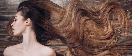 Donna con bei capelli lunghi su fondo di legno. Capelli lunghi. Tagli di capelli alla moda. Salone di bellezza per parrucchieri. Archivio Fotografico