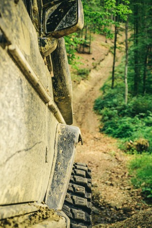 Bottom view to big offroad car wheel on country road and mountains backdrop. Offroad vehicle coming out of a mud hole hazard. Off-road vehicle goes on the mountain. Stock Photo