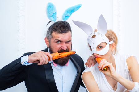 Happy easter and funny easter day. Bunny rabbit ears costume. Surprised bunny couple wearing bunny ears and eat carrot.