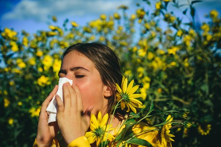 The girl suffers from pollen allergy during flowering and uses napkins. Flowering trees in background. Pretty woman got flu sneezing nose. Allergy. Closeup portrait.