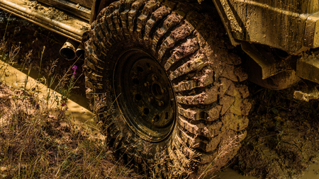 Best Off Road Vehicles. Off-road vehicle goes on the mountain. Bottom view to big offroad car wheel on country road and mountains backdrop. Road adventure. Adventure travel.