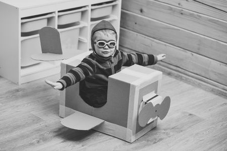 Pilot travel, airdrome, imagination. Air mail delivery, aircraft construction. Kid, pilot school, innovation. Dream, career, adventure, education. Little boy child play in cardboard plane, childhood. Banco de Imagens
