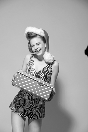 Christmas woman with red lips, black Friday. Happy retro girl celebrate new year and hold present box. Woman in santa hat with gift pack. Xmas party and winter holiday. Boxing day and Christmas. Stock Photo