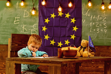 School break. Little boy drawing at table during school break. Child enjoy school break. School break in classroom with eu flag on chalkboard. I draw pictures all day.
