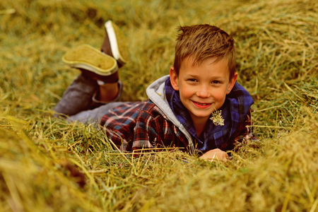Agriculture is in my heart. Little boy relax in hayloft. Little boy enjoy free time in countryside. Go organic and natural. Bring diversity back to agriculture.