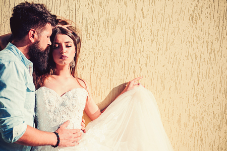 They love fashion and glamour. Romantic couple in love. Sensual bride in white wedding dress. Bearded groom in casual wear. Man and woman of fashion. Couple of lovers with fashion style.