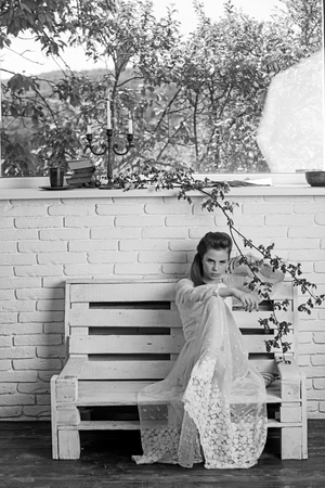 Beautiful young Parisian woman in long white silk dress sitting on the bench summer day