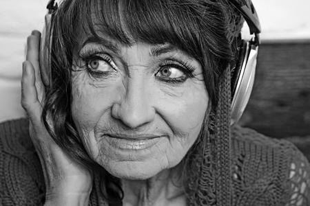 Old woman listen music in headphones.