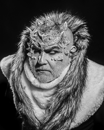Senior man with white beard dressed like monster. Alien, demon, sorcerer makeup. Dark arts concept. Demon on black background, close up. Man with thorns or warts in fur coat. Stock Photo