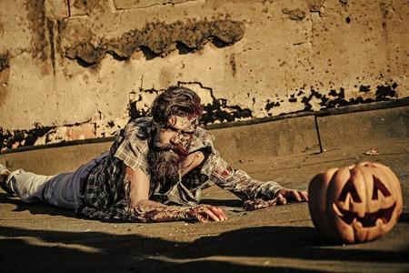 Zombie man lies on pumpkin