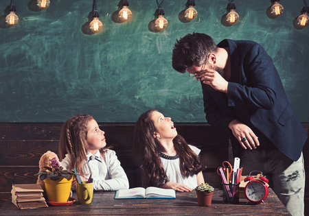 Bearded man and small girls in elementary school. Teacher teach schoolgirls in classroom. Children students study at desk. Teacher and pupils at lesson. Education and school concept
