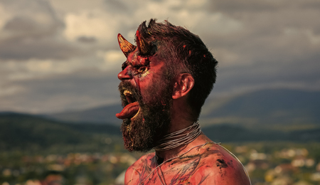 Halloween demon man with beard showing tongue