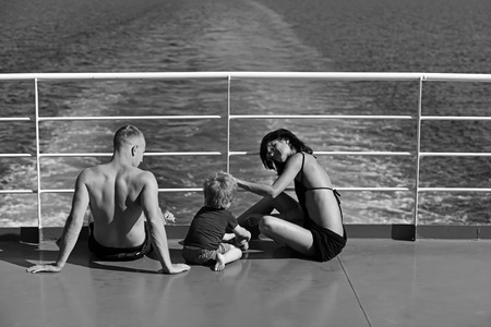 Summer vacation of happy family. Mother and father with son in sea on yacht. Family travel with kid on mothers or fathers day. Love and trust as family values. Child with father and mother