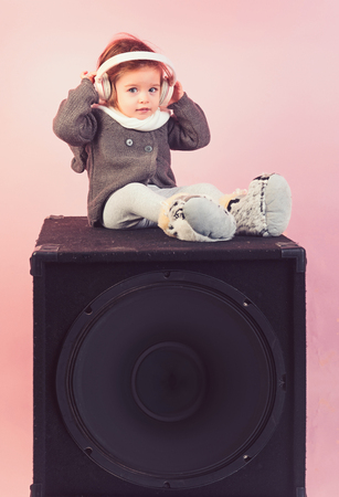 childhood and happiness. kid listen music with headset and mp3 on phone. small happy girl. audio speaker. little girl child smiling. winter kid fashion. having fun. Perfect song. She got great style Banque d'images - 117233931