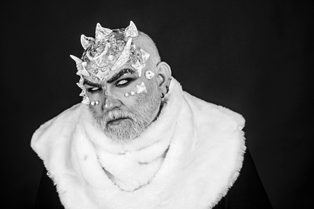 Demon on black background, close up. Man with thorns or warts in fur coat. Alien, demon, sorcerer makeup. Dark arts concept. Senior man with white beard dressed like monster, copy space.