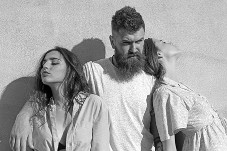 Man with beard hugs two ladies on hot sunny day. Threesome suffers of heat on summer day, wall on background. Girls turned to opposite sides while man hugs them. Love triangle concept.
