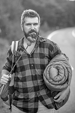 Hitchhiker on the way back to town. Bearded man with rucksack, sleeping back eating sausages from stick. Summer hiking in forest