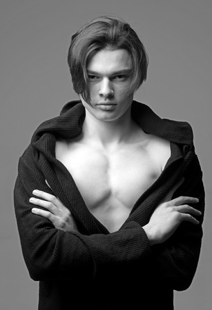 Man with smooth skin on face, neck and chest looking at camera. Guy on confident face in black bathrobe holds arms folded, grey background. Macho with stylish long haircut. Masculinity concept.