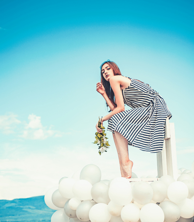 woman in summer dress with party balloons. inspiration and imagination. girl with flowers sit in sky. feeling freedom and dreaming. Fashion portrait of woman. Sexy beauty