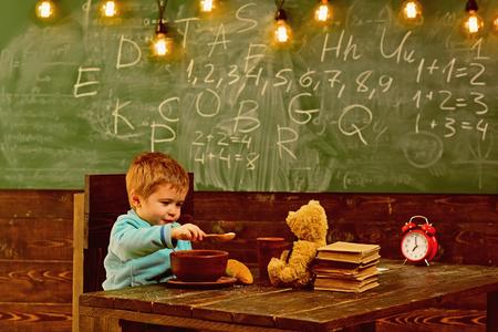 Little child feeding teddy bear in school. Boy feeding and taking care of toy friend in classroom. Stock Photo