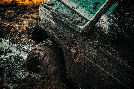 Véhicule tout-terrain va sur la montagne. Vue de dessous de la grande roue de voiture tout-terrain sur fond de route de campagne et de montagnes. Pistes sur un terrain boueux. Véhicule tout-terrain sortant d'un danger de trou de boue. Banque d'images