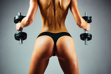 Attractive female doing biceps curl with dumbbells in the gym. Female fitness model. Healthy woman doing workout