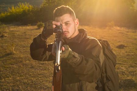 Hunting gun. Hunter with shotgun gun on hunt. Calibers of hunting rifles. Track down. Portrait of hamdsome Hunter.