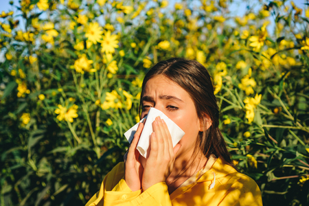 Sneezing young girl with nose wiper among blooming flowers in park. Young woman got nose allergy, flu sneezing nose. The girl suffers from pollen allergy during flowering and uses napkins. Allergy. Stock fotó