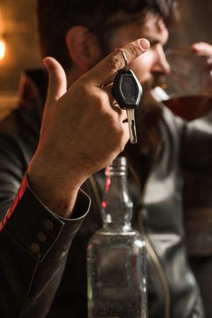 Macho drinken. Zelfverzekerde man met autosleutels in zijn hand. Niet drinken en rijden Bijgesneden afbeelding van dronken man pratende autosleutels.