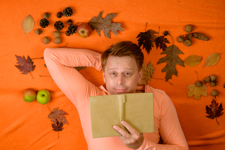 Young cute man lies on a wooden floor with autumn leaves and read book. Handsome man lies laying his hands behind head and resting on wooden floor in golden leaves. Portrait of handsome funny man.