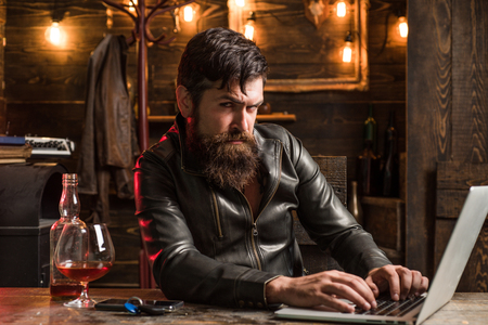 Portrait of a handsome man with beard. Brutality and masculine concept. Barbershop, shaving.Macho is drinking by his laptop. Doubt. Thinking. Stock Photo
