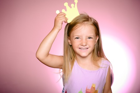 Cute little girl in a princess costume. Cheerful little girl with long blonde hair in tulle skirt holding princess crown on head isolated on pink background. Young pretty girl kid in pink dress.