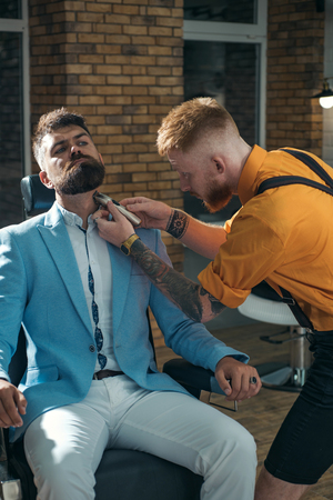 Bearded man or hipster. Ideas about Barbershop and Barber salon. Making haircut look perfect in barber shop. Fine Cuts. Professional hairstylist in barbershop interior.