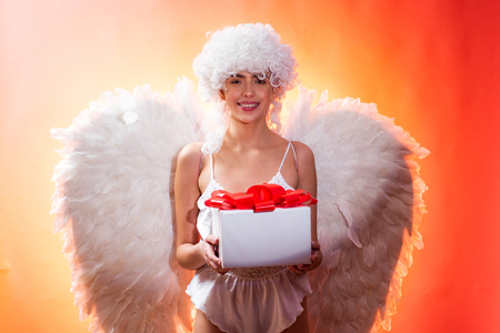 Valentines day concept. Angel with gift. Art photo of a Angelic beautiful woman. Angel woman with feather white wings and gift. Love concept. Stock fotó