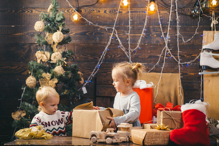Cute little child girl is decorating the Christmas tree indoors. Christmas kids. Portrait of happy child looking at decorative toy ball by Christmas tree.