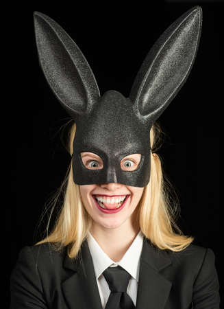 Happy easter. Bunny ears concept. Sexy woman wearing a black Easter Bunny. Beautiful young woman with bunny ears and blank poster on black background isolated. Stock Photo