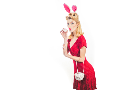 Easter egg hunting. Woman wearing a mask Easter bunny and looks very sensually. Happy Easter. Pin up Easter. Bunny woman. Stok Fotoğraf - 119759787