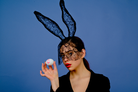 Lipstick kiss print on easter egg. Fashion woman in bunny ears with easter egg. 写真素材