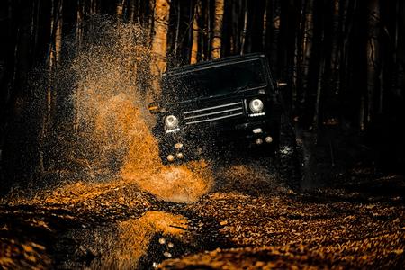 Off-road voertuig gaat op de berg. Modder en water spatten in off-road racen. Dragracewagen verbrandt rubber. Extreem. Off-road auto. Beste off-road voertuigen. Rally racen. Stockfoto