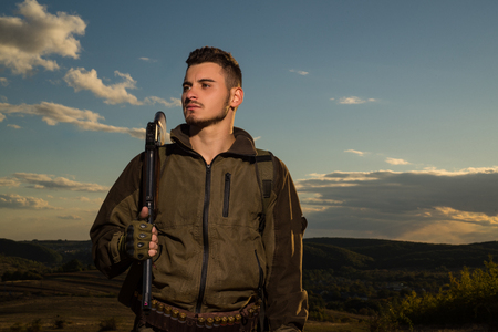 Young hunter. American hunting rifles. Hunting without borders. Hunter with shotgun gun on hunt. Portrait of handsome Hunter. Stock Photo
