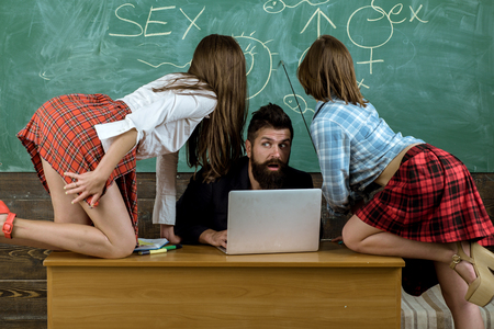 Sexology teacher looks at two female students. Erotic education and Symbols on chalkboard.