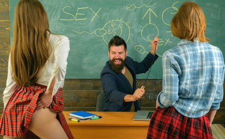 Sexology teacher looks at two sexy female students. Erotic education. Education and sex Symbols on chalkboard. Lesson and sex education in high school.