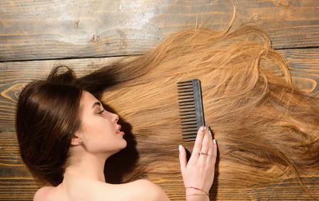 Ritratto della donna del primo piano con capelli molto lunghi, spazio della copia. Donna con bei capelli lunghi su fondo di legno. Capelli lunghi.