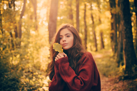 Beautiful Autumn Woman with Autumn Leaves on Fall Nature Background. Hello Autumn. Outdoor atmospheric fashion photo of young beautiful lady in autumn landscape. Stok Fotoğraf
