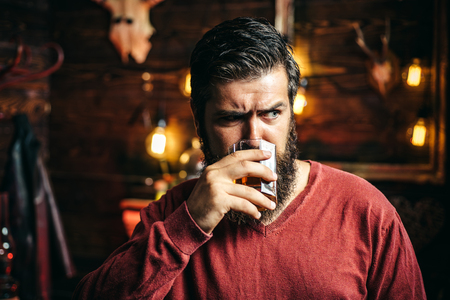 Man with alcohol drink at home. Drinking man. Barman hipster. Alcohol addiction. Stock Photo