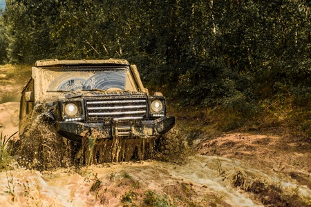 car crashed into a puddle and picked up a spray of dirt. Off road sport truck between mountains landscape. Track on mud. 4x4 Off-road suv car. Offroad car. Safari. Best Off Road Vehicles.