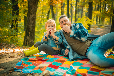 Happy family, father and baby son playing and laughing on autumn walk. Father playing with little son on a picnic in the park in early autumn day.