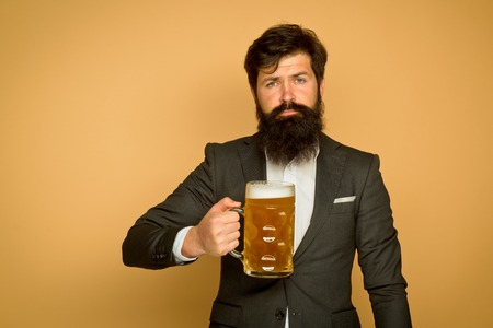 Bearded man in black suit with a glass of beer. Happy elegant man drinking beer. Beer pubs and bars. Bearded man drinking lager beer.