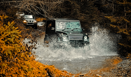 Mud and water splash in off-road racing. Off road sport truck between mountains landscape. Expedition offroader. Tracks on a muddy field. Road adventure. Adventure travel.