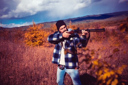 Autumn hunting season. Hunter with shotgun gun on hunt. Hunter with Powerful Rifle with Scope Spotting Animals.